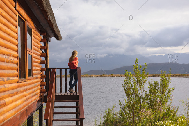 Side view of a Caucasian woman having a good trip to the mountains, standing on a balcony in a cabin, leaning on a barrier