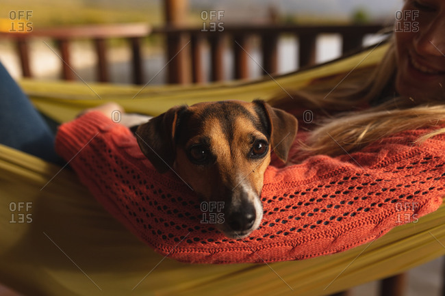 Side view close up of a Caucasian woman having a good time on a trip to the mountains, lying on a hammock, with a puppy on her belly