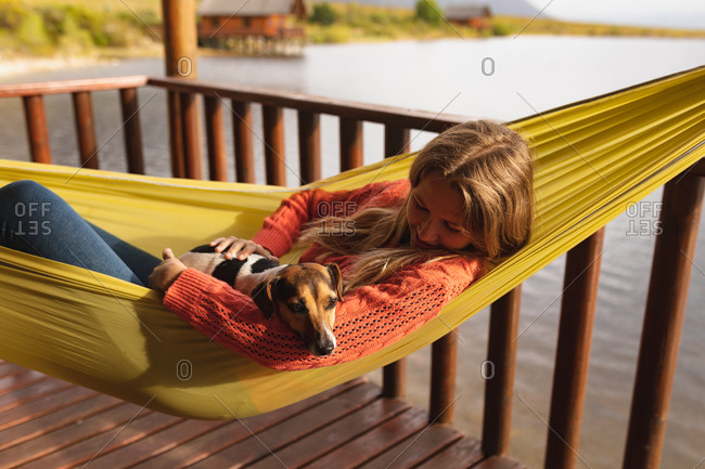 Side view of a Caucasian woman having a good time on a trip to the mountains, lying on a hammock, with a puppy on her belly