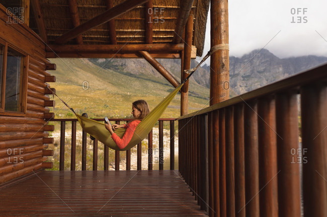 Side view of a Caucasian woman having a good time on a trip to the mountains, lying on a hammock, using a digital tablet