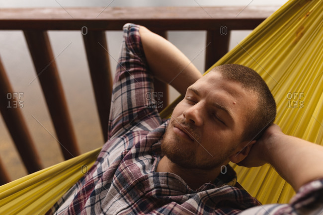 Front view close up of a Caucasian man having a good time on a trip to the mountains, lying on a hammock with his eyes closed and hands beneath the head