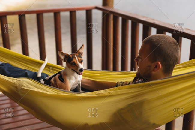 Side view close up of a Caucasian man having a good time on a trip to the mountains, lying on a hammock with a puppy on his chest