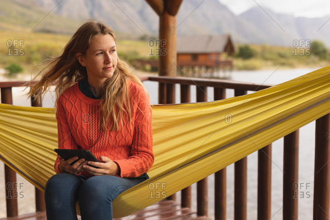 Front view of a Caucasian woman having a good time on a trip to the mountains, sitting on a hammock, using a digital tablet