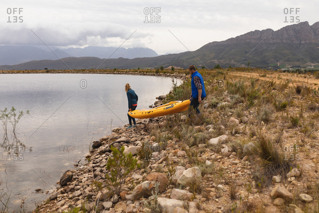 Side view of a Caucasian couple having a good time on a trip to the mountains, holding a kayak up, preparing to put it on the water