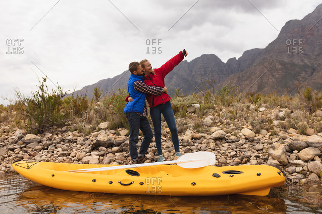 Side view of a Caucasian couple having a good time on a trip to the mountains, embracing and taking a selfie after putting a kayak onto the water