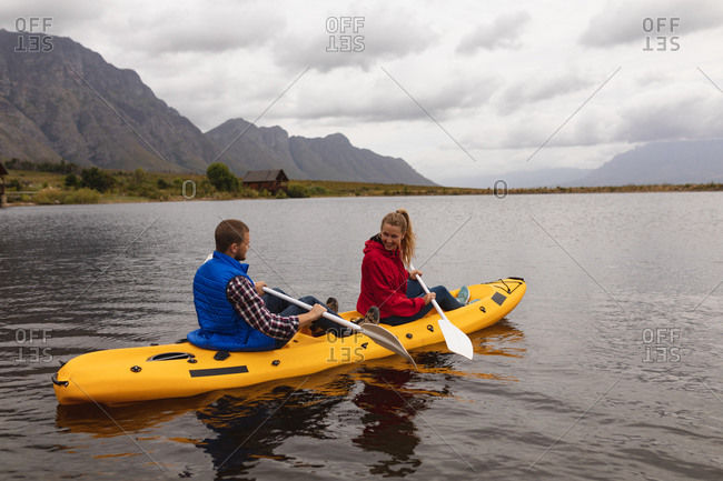 Side view of a Caucasian couple having a good time on a trip to the mountains, kayaking on a lake, looking at each other