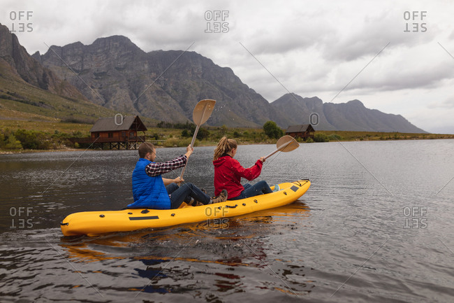 Side view of a Caucasian couple having a good time on a trip to the mountains, kayaking on a lake