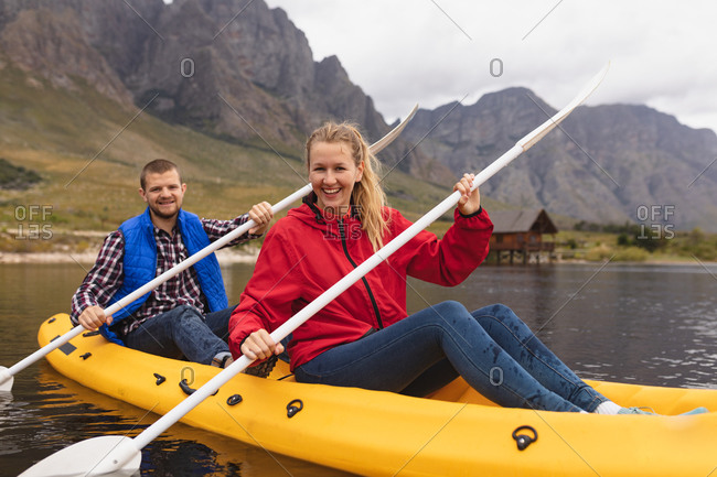 Front view of a Caucasian couple having a good time on a trip to the mountains, kayaking on a lake, smiling