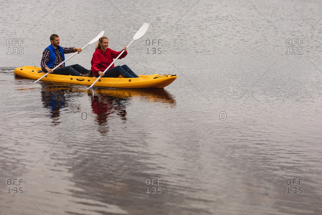 High angle side view of a Caucasian couple having a good time on a trip to the mountains, kayaking on a lake, smiling