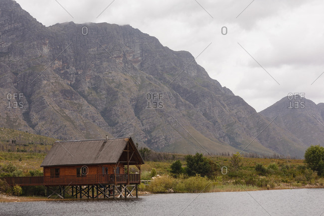 Breathtaking view of a cabin standing lonely by a lake with magnificent mountains behind it and a field between them