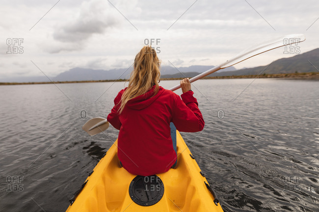 Rear view of a Caucasian woman having a good time on a trip to the mountains, kayaking on a lake, enjoying her view