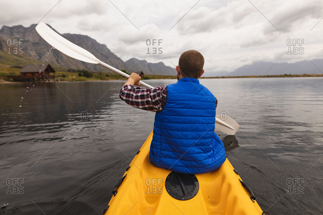 Rear view of a Caucasian man having a good time on a trip to the mountains, kayaking on a lake, enjoying his view