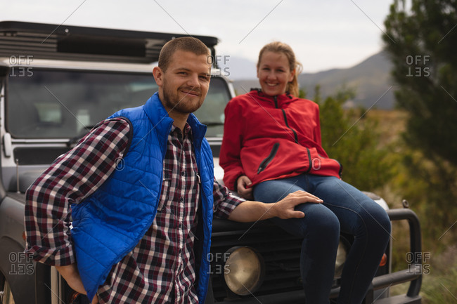 Front view of a Caucasian couple having a good time on a trip to the mountains, a woman is seating on a car hood and a man is holding her thigh, looking at the camera