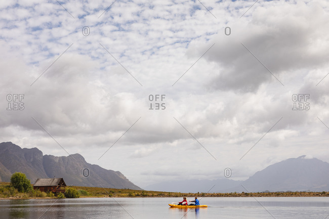 Side view of a Caucasian couple having a good time on a trip to the mountains, kayaking on a lake, with a cabin in the background