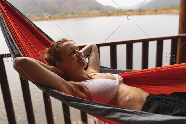 Side view of a Caucasian woman having a good time on a trip to the mountains, lying on a hammock on a balcony in a cabin, having her eyes closed, with hands behind her head