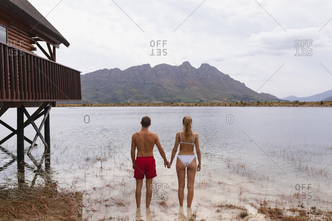 Rear view of a Caucasian couple having a good time on a trip to the mountains, standing in the lake, holding hands