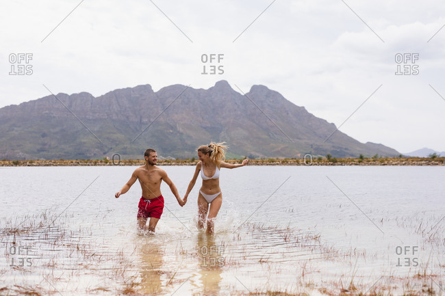 Front view of a Caucasian couple having a good time on a trip to the mountains, running in the lake, holding hands