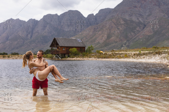 Front view of a Caucasian couple having a good time on a trip to the mountains, standing in a lake, a man is holding a woman