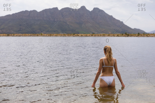 Rear view of a Caucasian woman having a good time on a trip to the mountains, standing in a lake, enjoying her view