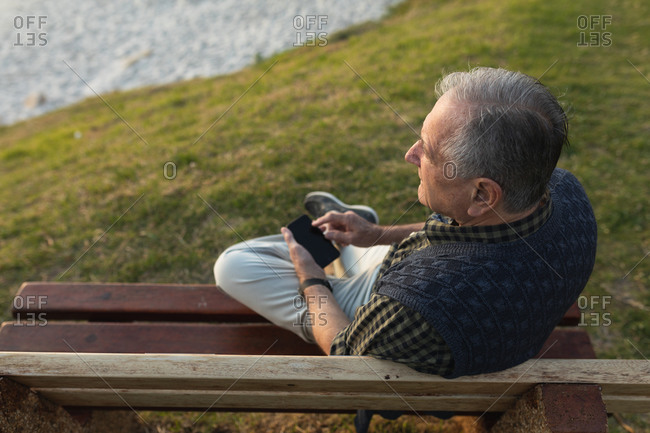 High angle view of a senior Caucasian man relaxing, sitting on a bench in the countryside by the sea admiring a coastal view and using a smartphone