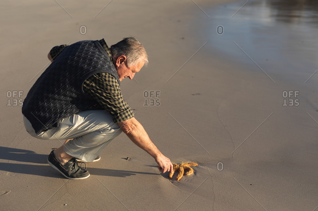 Side view of a senior Caucasian man exploring alone on a beach, squatting down and reaching out to touch a starfish, stranded on the sand