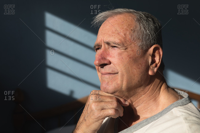 Side view close up of a senior Caucasian man relaxing at home in his bedroom, sitting in the sun and thinking, after getting up in the morning