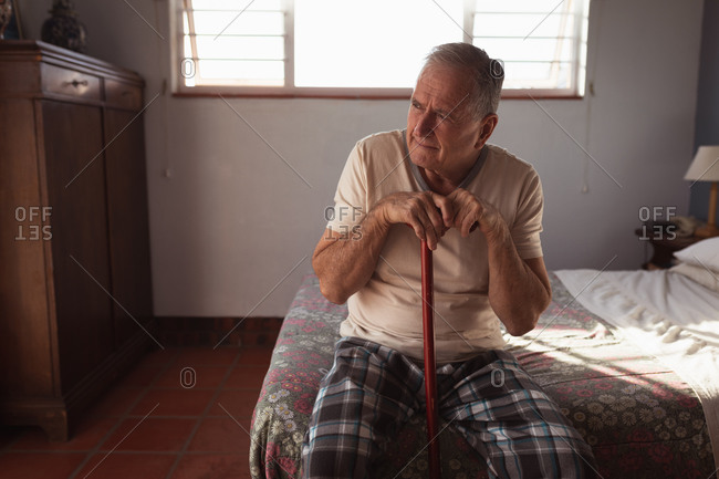 Front view of a senior Caucasian man relaxing at home in his bedroom, sitting on the side of the bed holding his cane and thinking after getting up in the morning