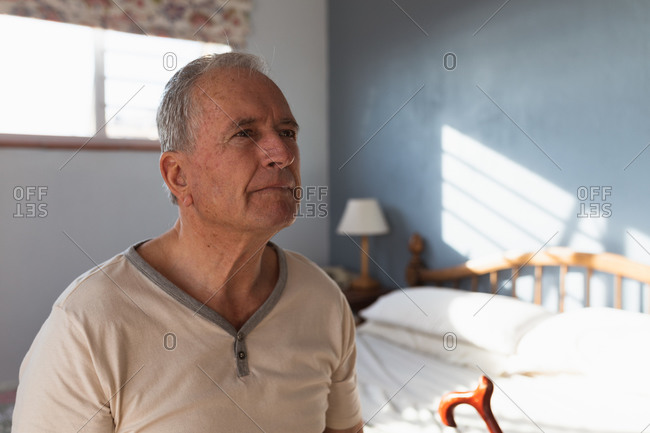 Side view close up of a senior Caucasian man relaxing at home in his bedroom, sitting on the side of his bed with his cane and thinking, after getting up in the morning