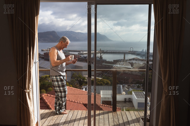 Side view of a senior Caucasian man relaxing at home wearing a vest and pajama trousers, standing on the balcony using a mobile phone and drinking coffee