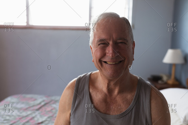 Portrait of a senior Caucasian man relaxing at home in his bedroom, wearing a vest and looking to camera smiling, with a sunlit window behind him