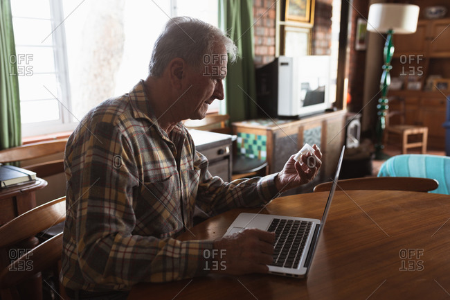 Side view of a senior Caucasian man relaxing at home in his living room, sitting at the table using a laptop computer and holding a bottle of tablets