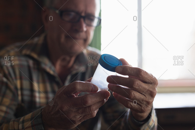 Front view close up of a senior Caucasian man sitting at home holding pill box of medication, focus on the foreground