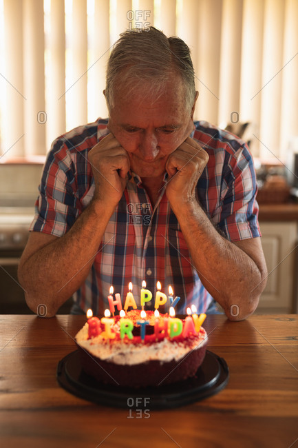 Front view of a senior Caucasian man at home, sitting alone at the dining table looking down at a birthday cake with lit candles on it