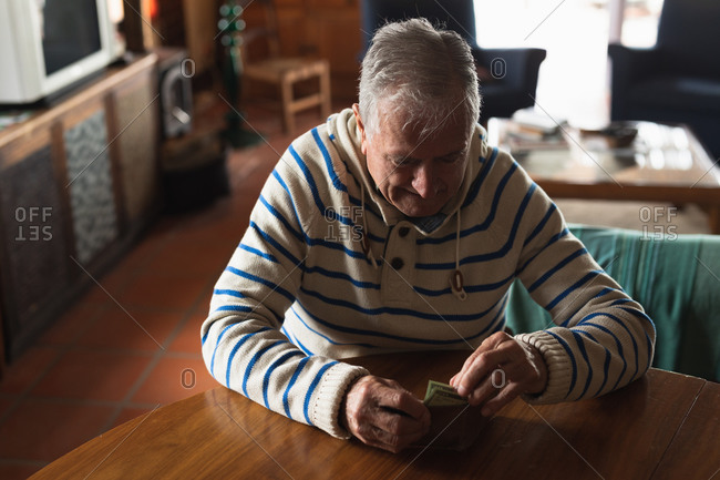 Front view of a senior Caucasian man at home, sitting at the table in his dining room, looking at and touching the money in his wallet