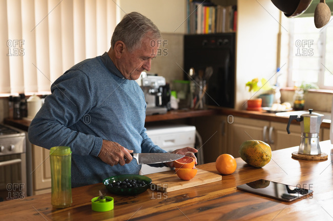 Side view of a senior Caucasian man relaxing at home, standing at the counter in his kitchen carefully slicing fruit in half with a sharp knife