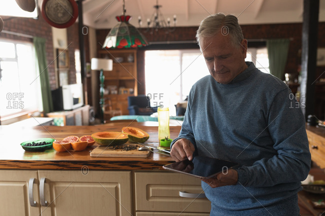 Front view of a senior Caucasian man relaxing at home, sitting at the counter in his kitchen, using a tablet computer