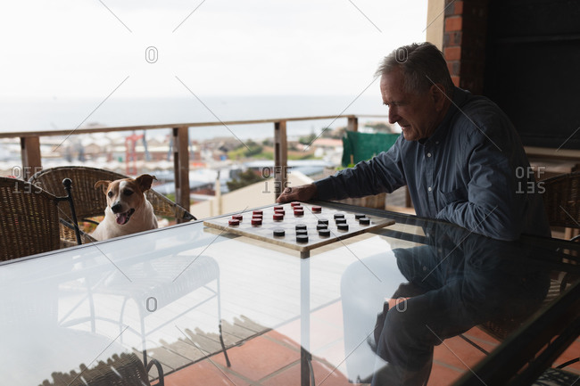 Side view of a senior Caucasian man relaxing at home, sitting at a table by the window playing draughts, his pet dog sitting on a chair opposite him watching