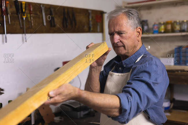 Side view of a senior Caucasian man relaxing at home, standing in his workshop, holding and checking a piece of wood, with tools hanging on the wall in the background