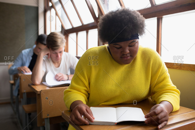 Front view of a teenage African American girl in a school classroom sitting at desk, concentrating and reading, with teenage male classmates sitting at desks working in the background