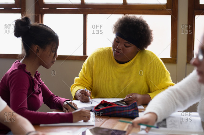 Front view of two teenage African American female school pupils in a classroom, sitting at a table working together and talking