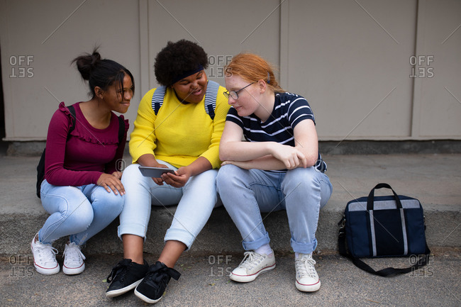 Front view of a multi-ethnic group of teenage female high school pupils with schoolbags hanging out, talking and looking at a smartphone together, sitting on steps in their school grounds