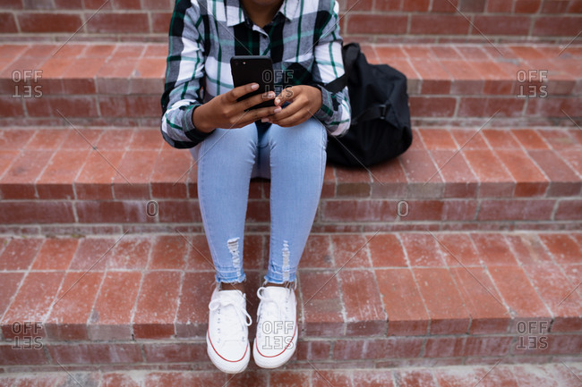 Low section front view close up of an African American teenage female high school student, using a smartphone and sitting on steps in the school grounds