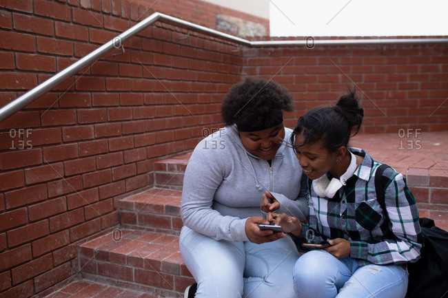 Side view of two high school African American teenage female school pupils, using a smartphone and sitting on steps in the school grounds