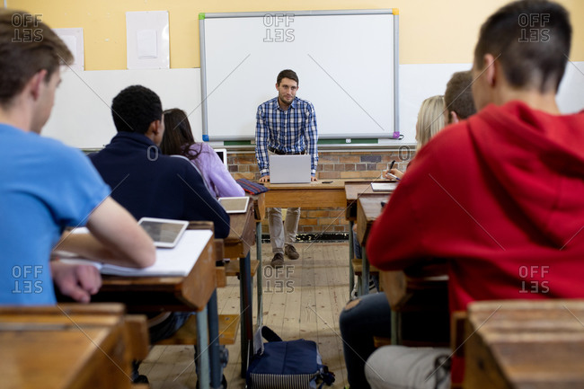 Front view of a male Caucasian teacher standing, using a laptop and talking to a multi-ethnic group of teenagers in a school high school classroom sitting at desks and listening