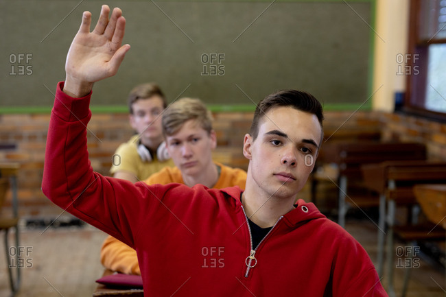 Front view of a teenage Caucasian boy in a high school classroom sitting at desk, raising his hand to answer a question, with teenage male classmates sitting at desks working in the background