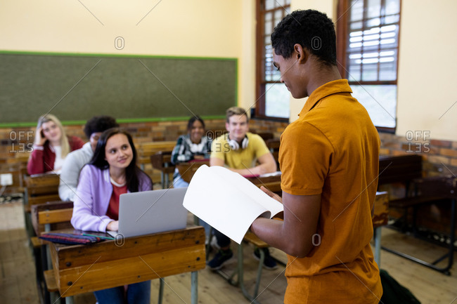 Side view of a teenage African American male high school student reading to a multi-ethnic class of teenagers sitting at desks in a school classroom listening and concentrating