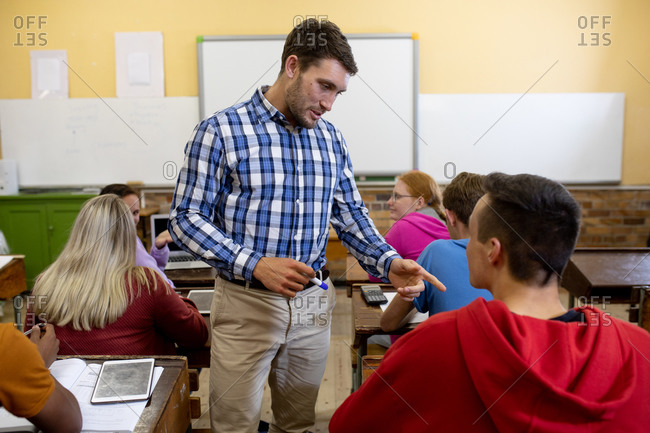 Front view of an male Caucasian teacher standing and talking to a Caucasian male student in a multi-ethnic class of teenagers in a high school classroom sitting at desks and working