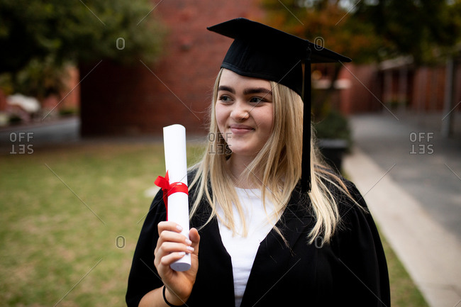 Front view of teenage Caucasian female high school student with long blonde hair wearing a cap and gown, holding a diploma and smiling on her graduation day