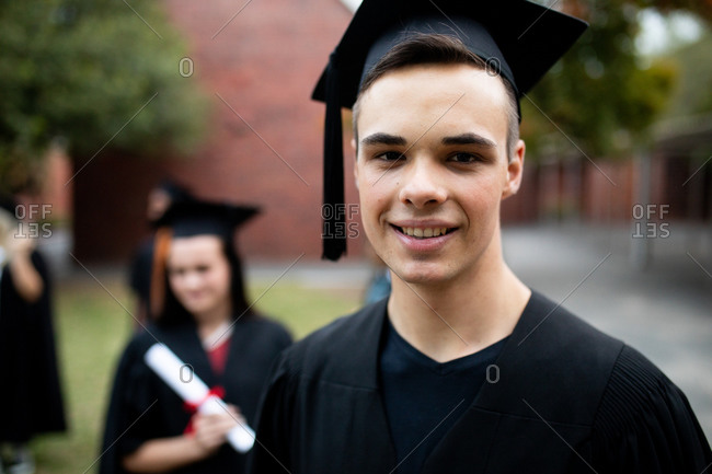 Portrait of teenage Caucasian male high school student wearing a cap and gown on his graduation day, looking to camera and smiling, with other students wearing caps and gowns in the background