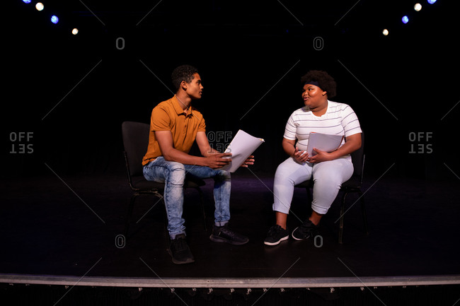 Side view of a mixed race teenage boy and African American teenage girl high school student sitting on chairs in an empty school theatre preparing before a performance, holding scripts and rehearsing together